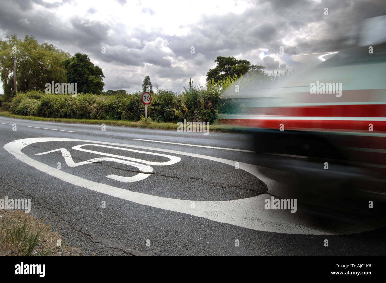 Blurred speeding car passes 30mph speed limit sign painted on road - Stock Image