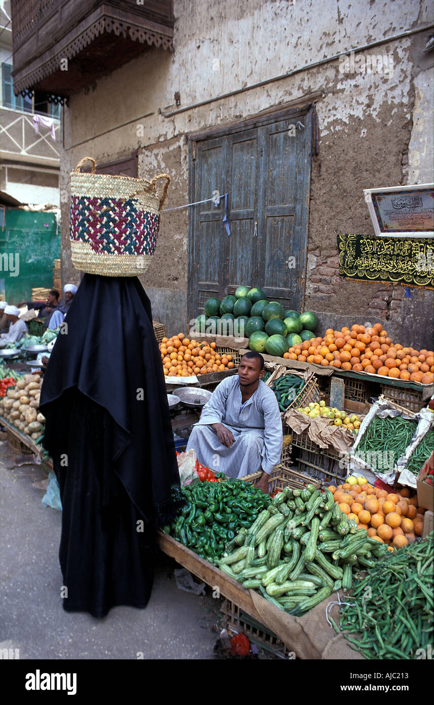 Fruit and vegetable vendor at his stall serving a muslim in purdah Luxor s street market Egypt Stock Photo