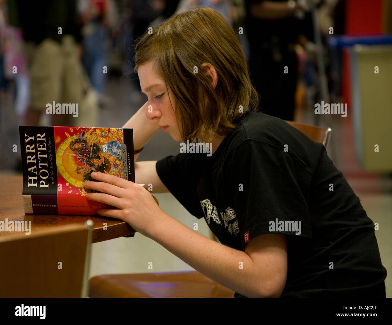child seated at table reading j k rowlings harry potter and the deathly hallows - Stock Image