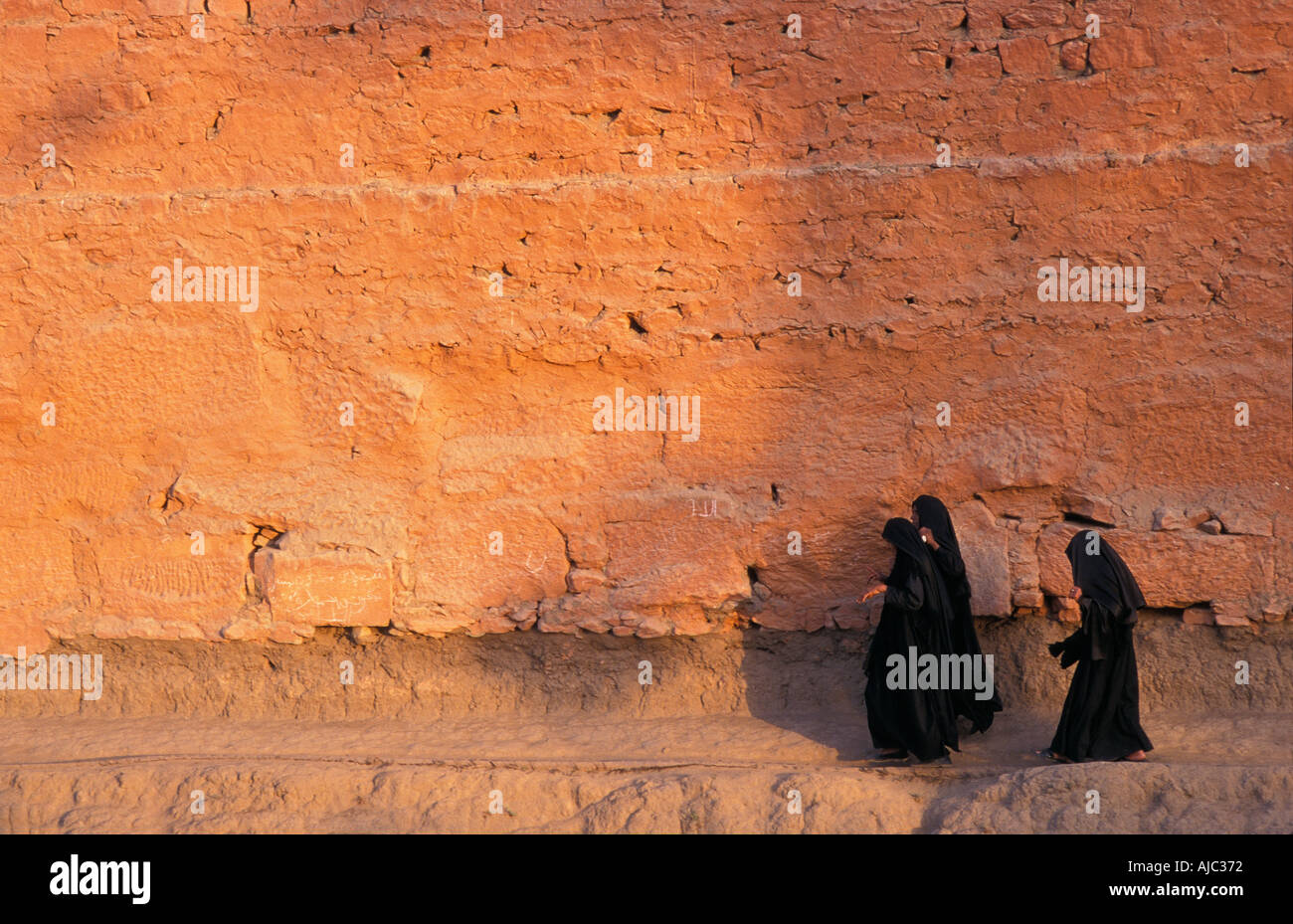 Muslim women robed in black burqas walking along the path around the pouter wall of Karnak Temple Upper Egypt Nr Luxor - Stock Image