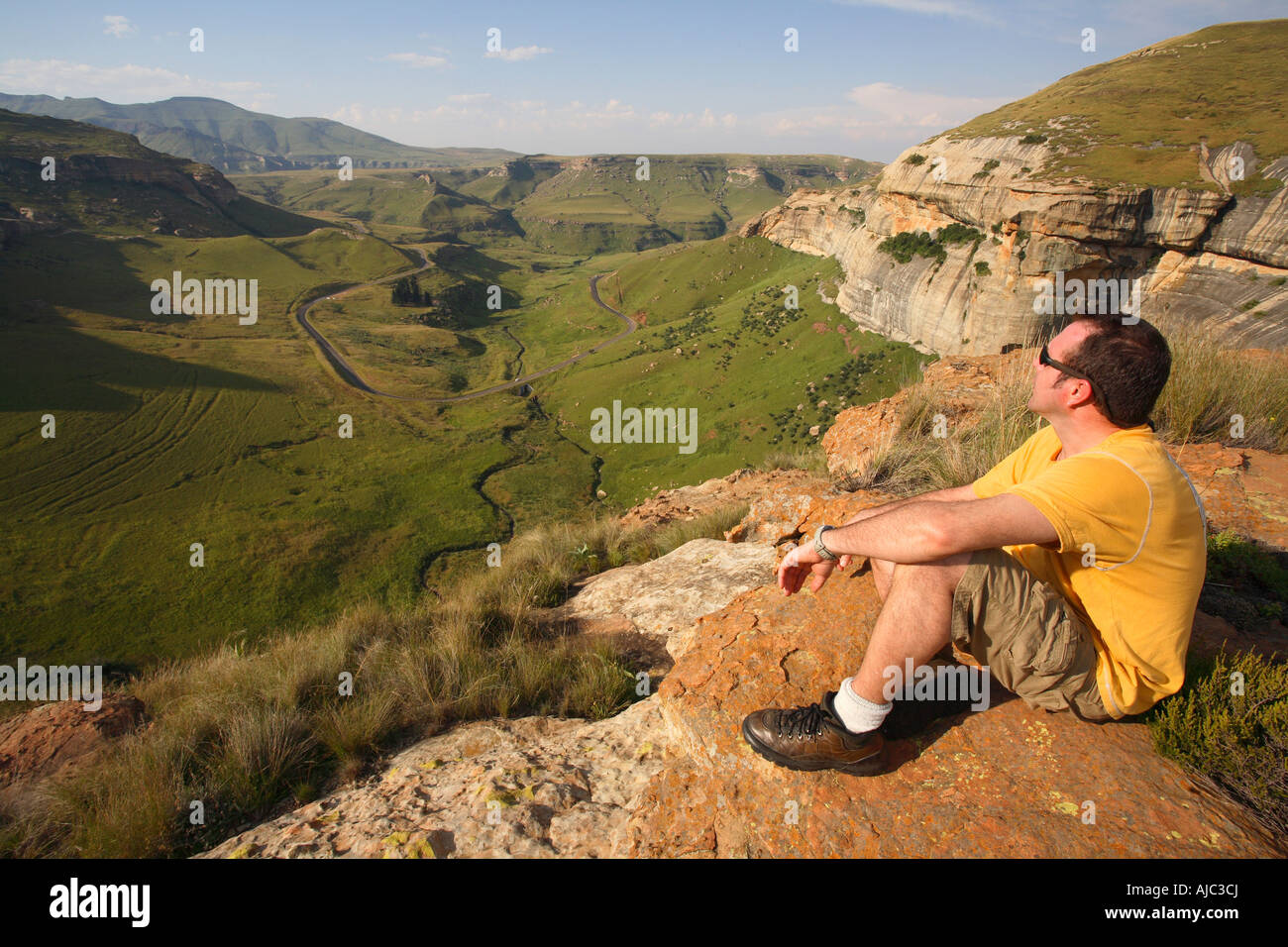 Man Sitting on a Rock Looking out on the Valley Bellow Stock Photo
