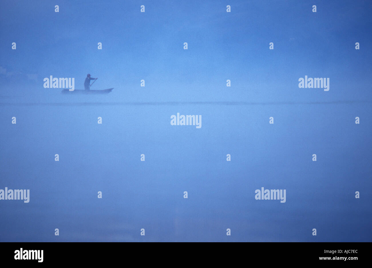 Fisherman slicing through the mist on a canoe at dawn Santiago Atitlan a Tzutuhil Maya community Lake Atitlan Guatemala - Stock Image