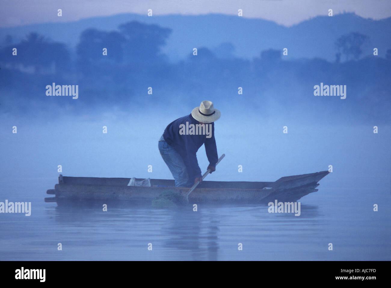 Dredging reeds from a canoe at dawn Santiago Atitlan a Tzutuhil Maya community Lake Atitlan Guatemala Stock Photo