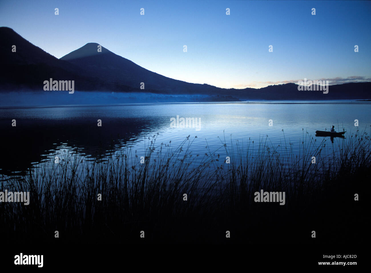 Santiago Atitlan sits beneath the towering peak of Toliman volcano Lone fisherman in canoe Lake Atitlan at dawn Guatemala - Stock Image