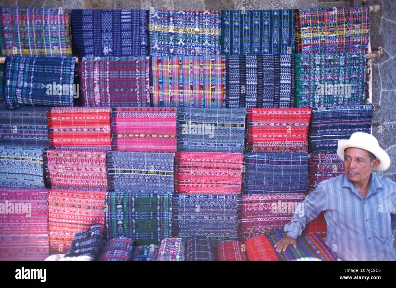 Weaver vendor selling a selection of hand woven skirts at market Santiago Atitlan Guatemala - Stock Image