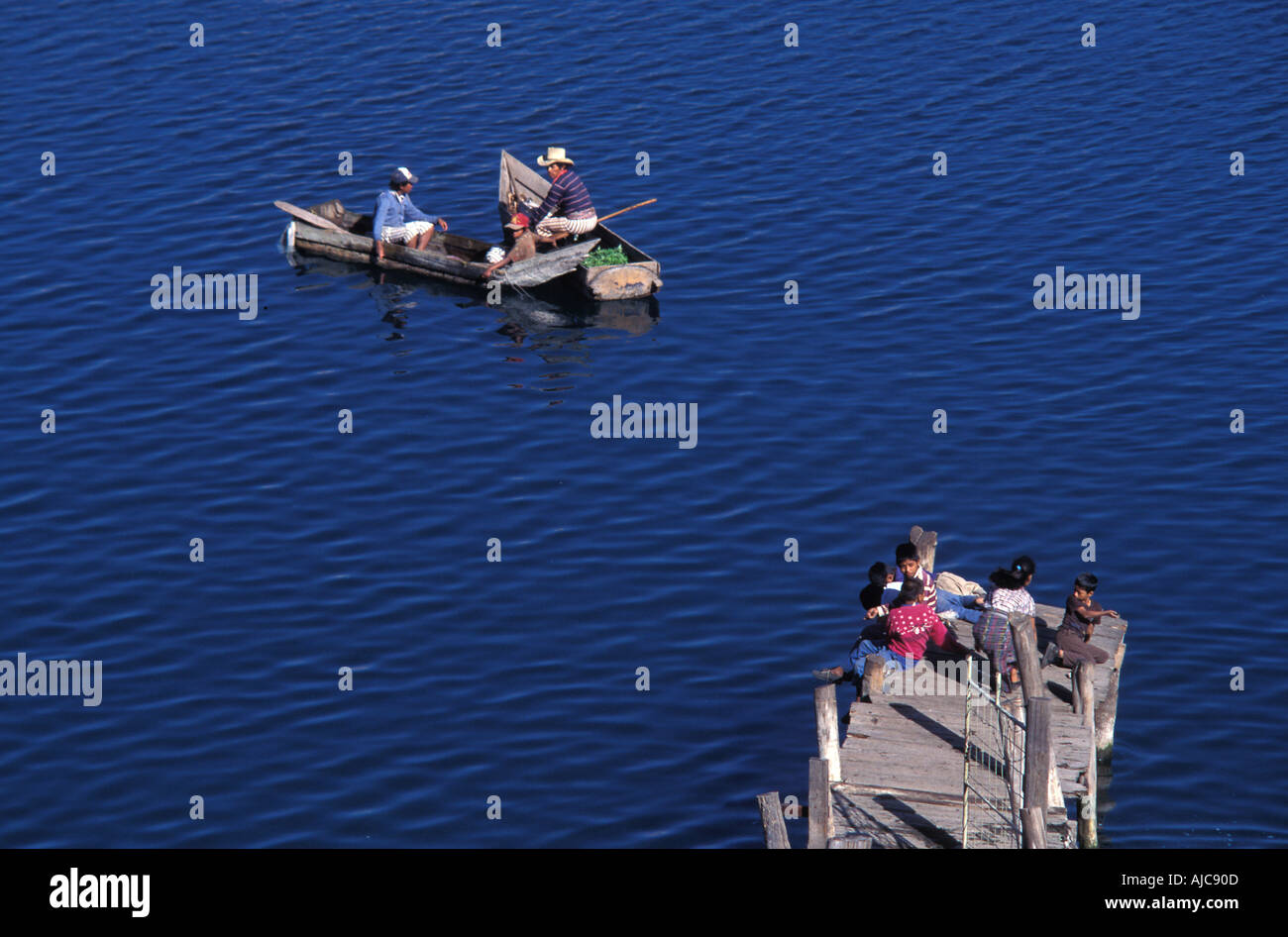 Fishing from canoe and jetty adults and kids get involved Santiago Atitlan Guatemala - Stock Image