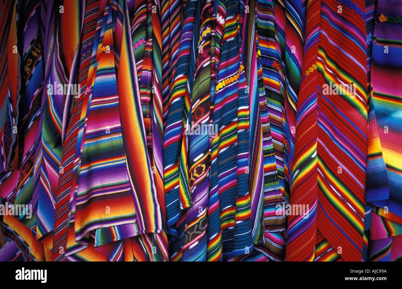 Selection of brightly coloured woven shawls zutes for sale at market Chichicastenango Guatemala Stock Photo