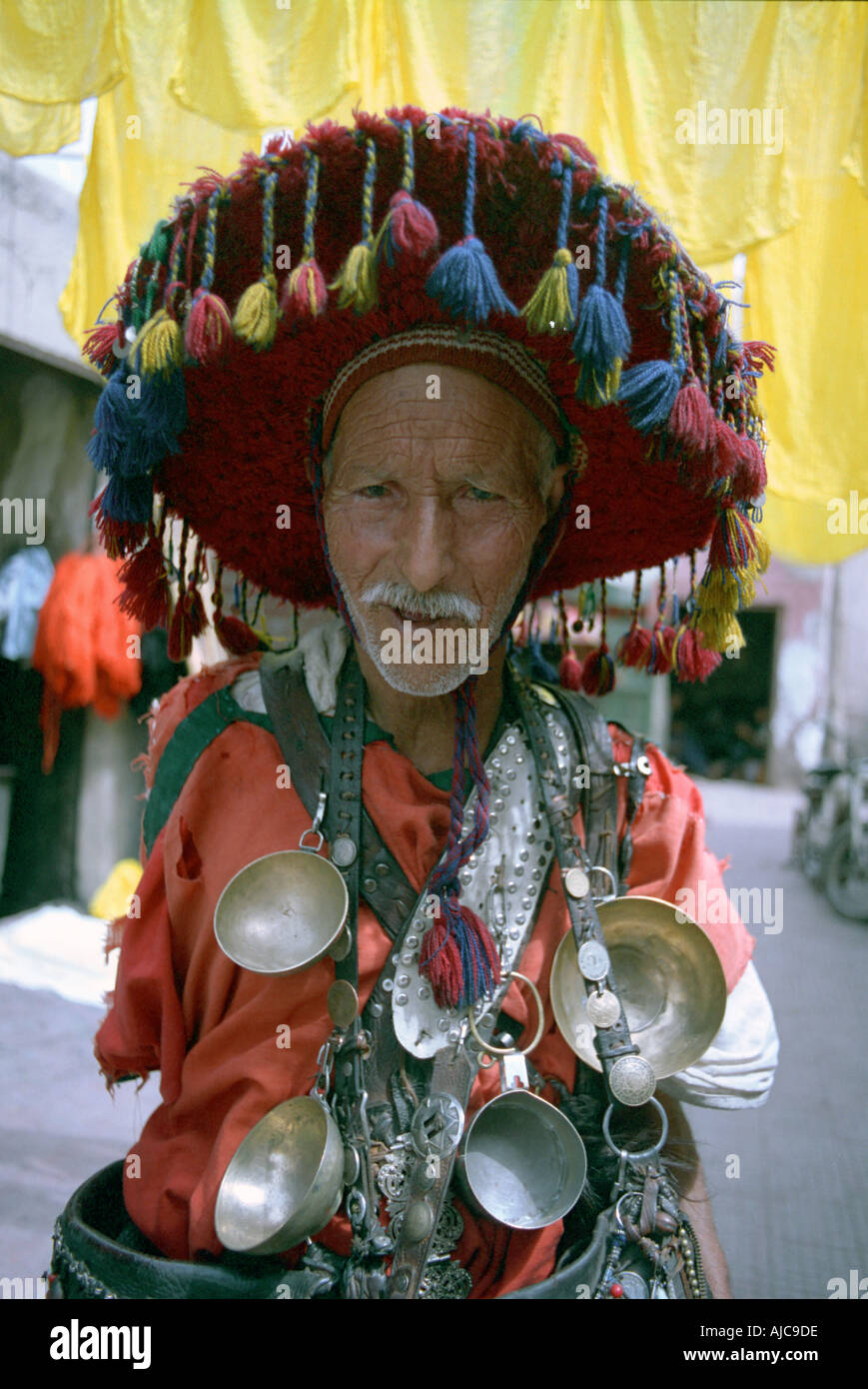 Water seller wearing bright attire in the souk of Marrakesh Morocco - Stock Image