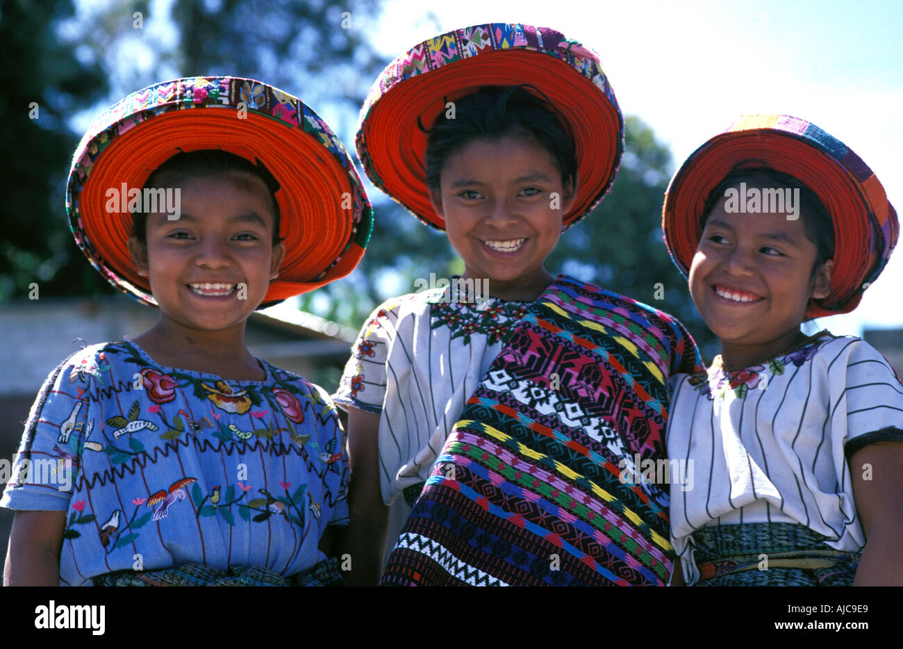 3 young girls in the distinctive tribal costume of their Tzutihil Maya community Santiago Atitlan Guatemala - Stock Image