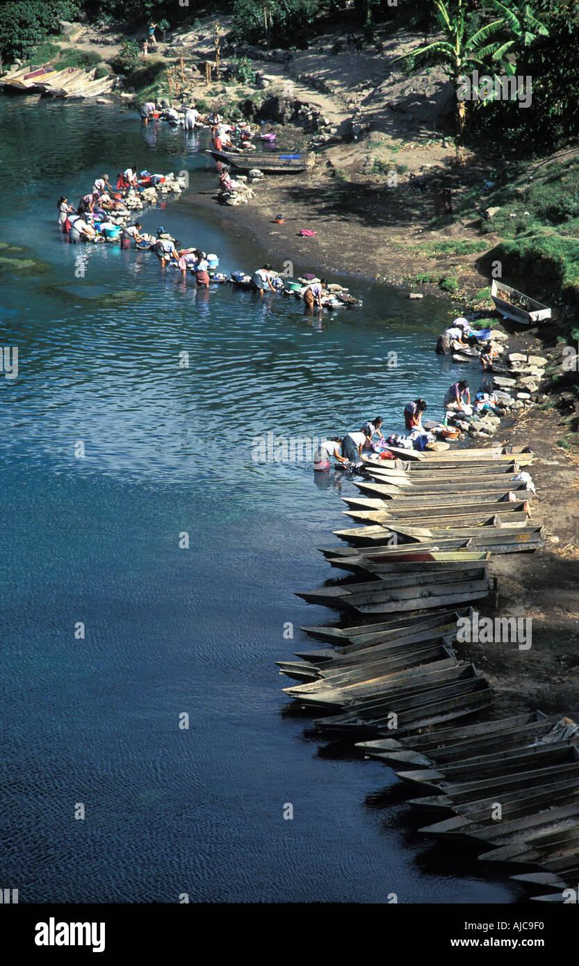 Maya women at the lakeshore washing their clothes Canoes line the shore Santiago Atitlan Lake Atitlan Guatemala - Stock Image