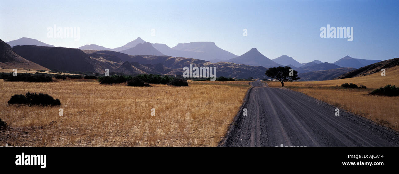 Panoramic landscape gravel roads Palmwag to Sesfontein Extinct volcanoes and tabletop mountains line the horizon Namibia - Stock Image