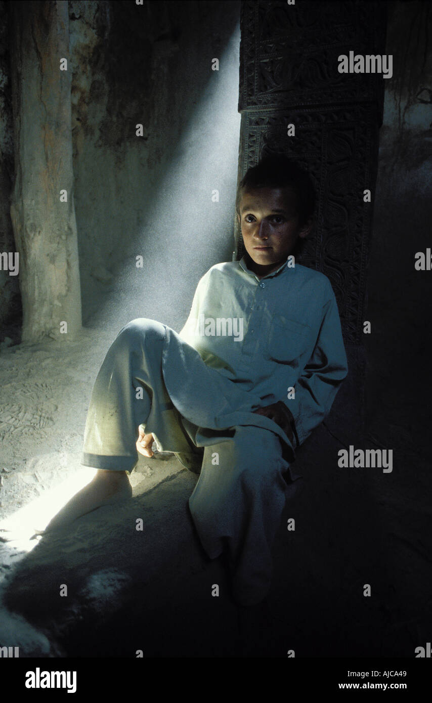 Pakistani boy from the Hunza valley photographed in a shaft of light at Altit Fort Karimabad - Stock Image