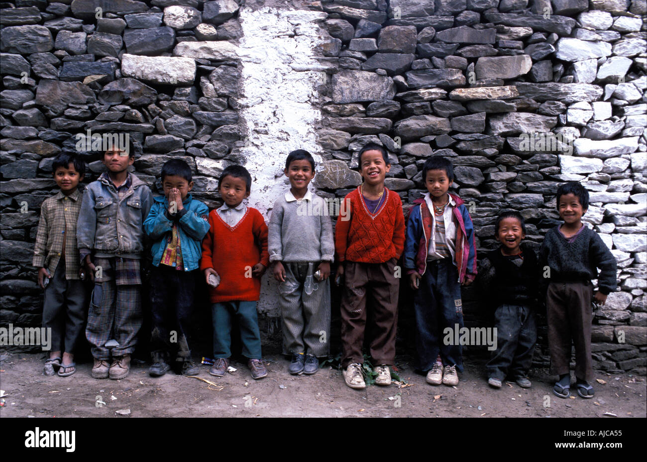 A group of boys from Keylong Himachal Pradesh foothills of the Himalayas lined up against a stone wall India - Stock Image