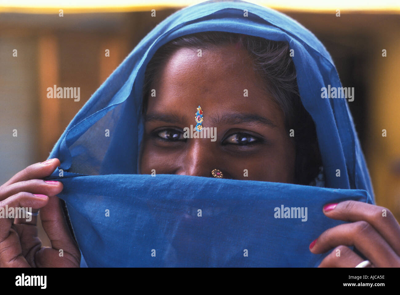 Friendly Hindu woman from Uttar Pradesh with blue headcloth veiling her smile India Photo By Jamie Marshall - Stock Image