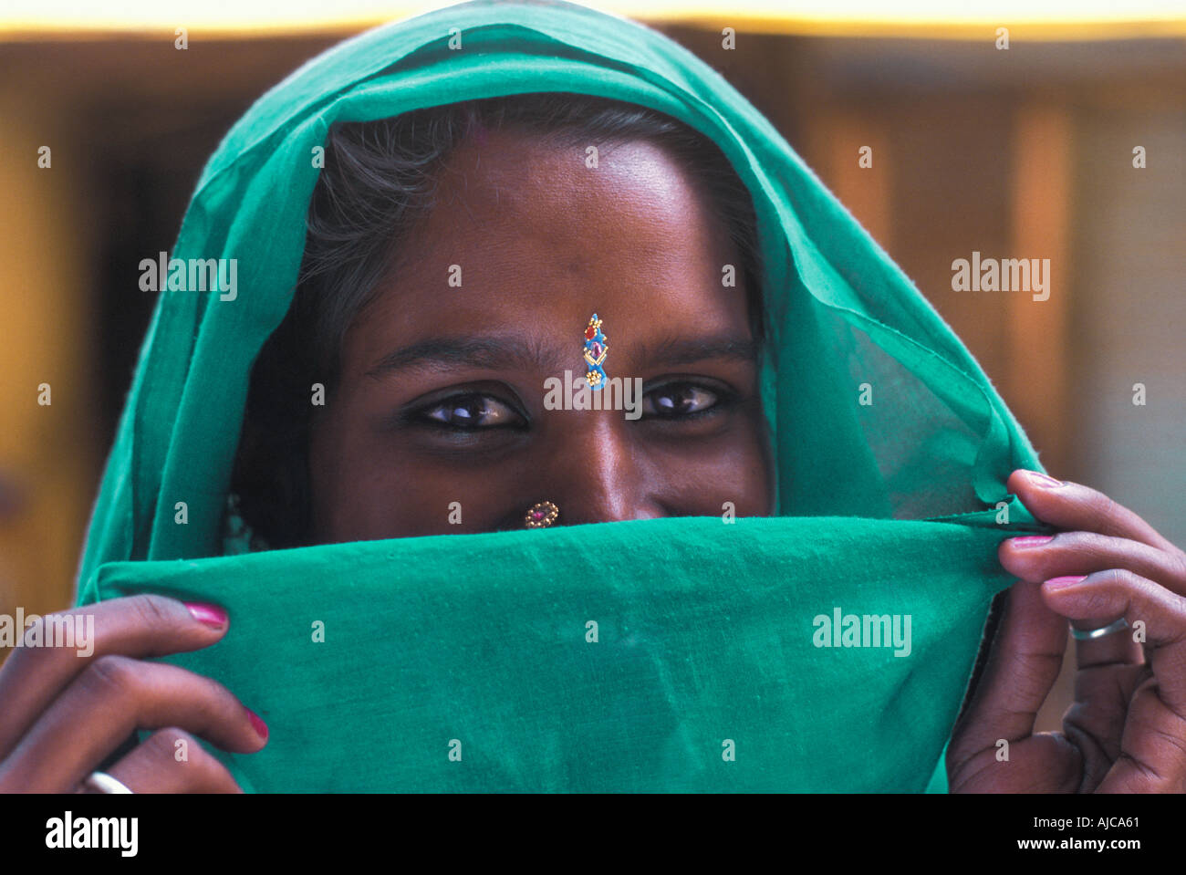 Friendly Hindu woman from Uttar Pradesh with green headcloth veiling her smile India - Stock Image