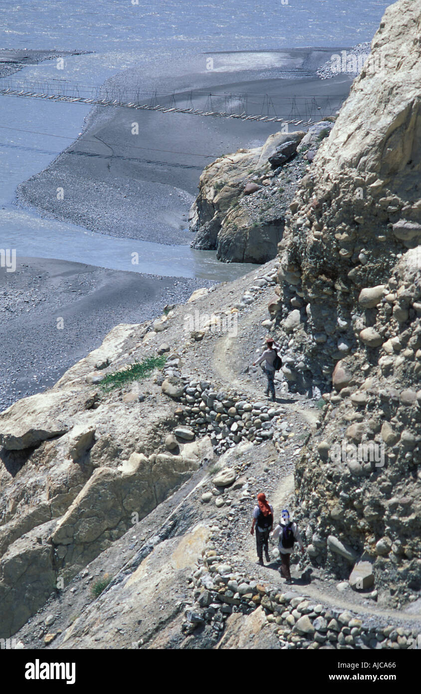 Backpackers approaching a suspended footbidg Trekking in and around Passu Gojal Upper Hunza N Pakistan Stock Photo