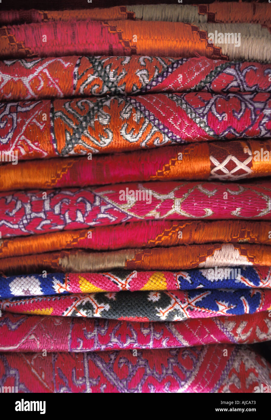 Stack of everyday and ceremonial hand embroidered silk and woven fabrics from Pakistan Stock Photo