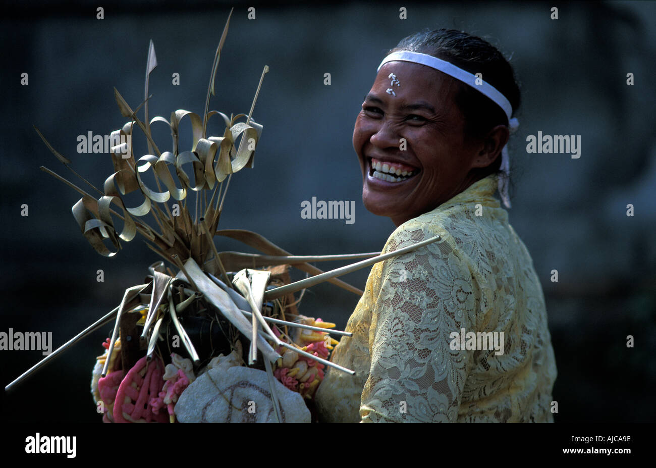 BALI Joyful Balinese woman arrives at the temple with a religious offering Full moon celebrations Ubud Bali Indonesia Stock Photo