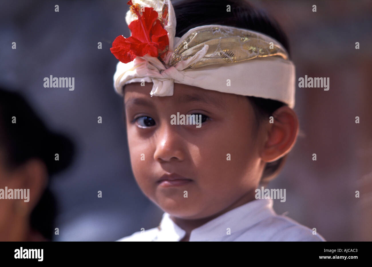 Young boy formally dressed and attending a temple on the occasion of full moon celebrations Ubud Bali Indonesia - Stock Image