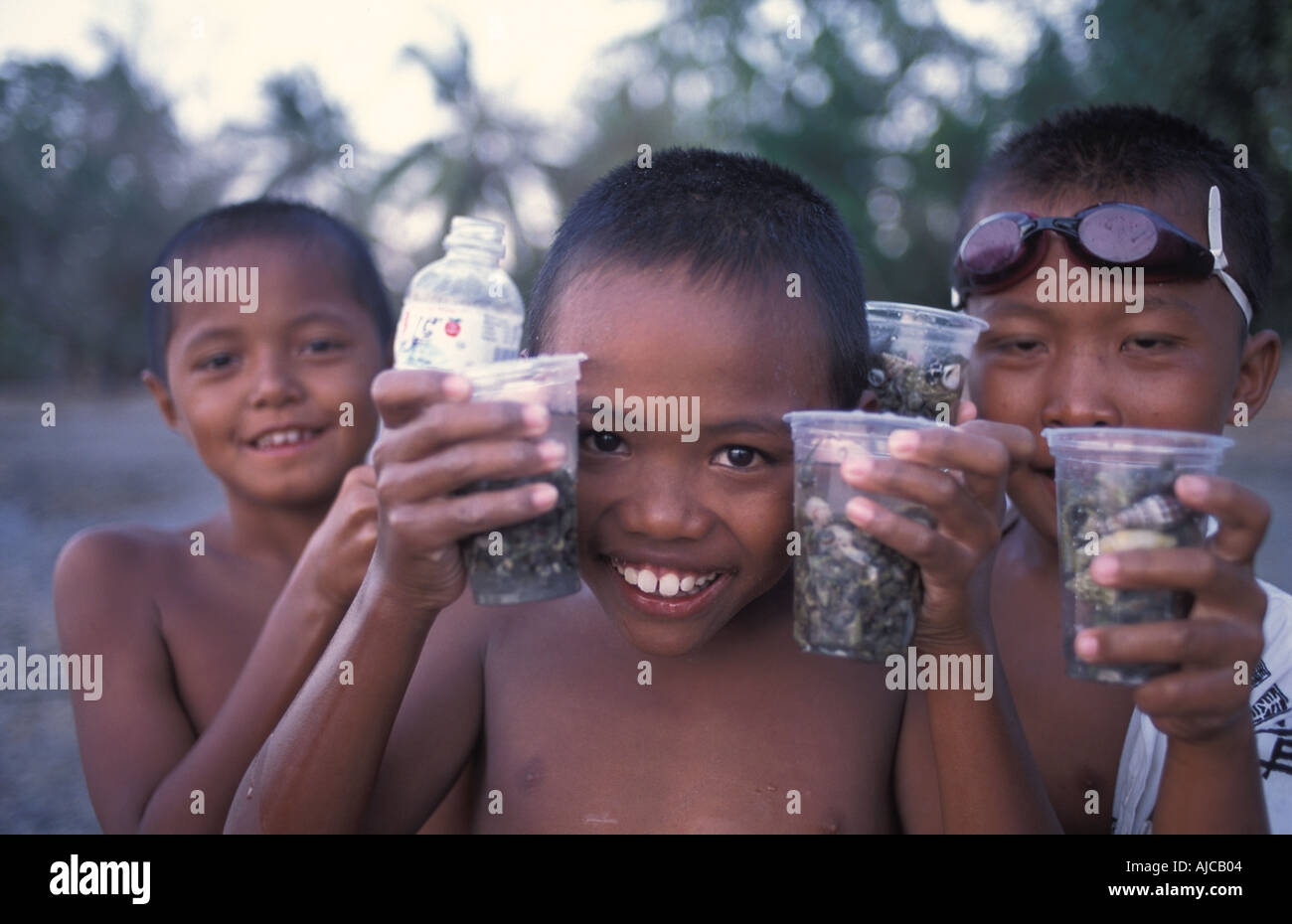 Balinese boys collect small crabs and shellfish Labuan Lalang the port for reaching Pulau Menjangan Deer Island - Stock Image