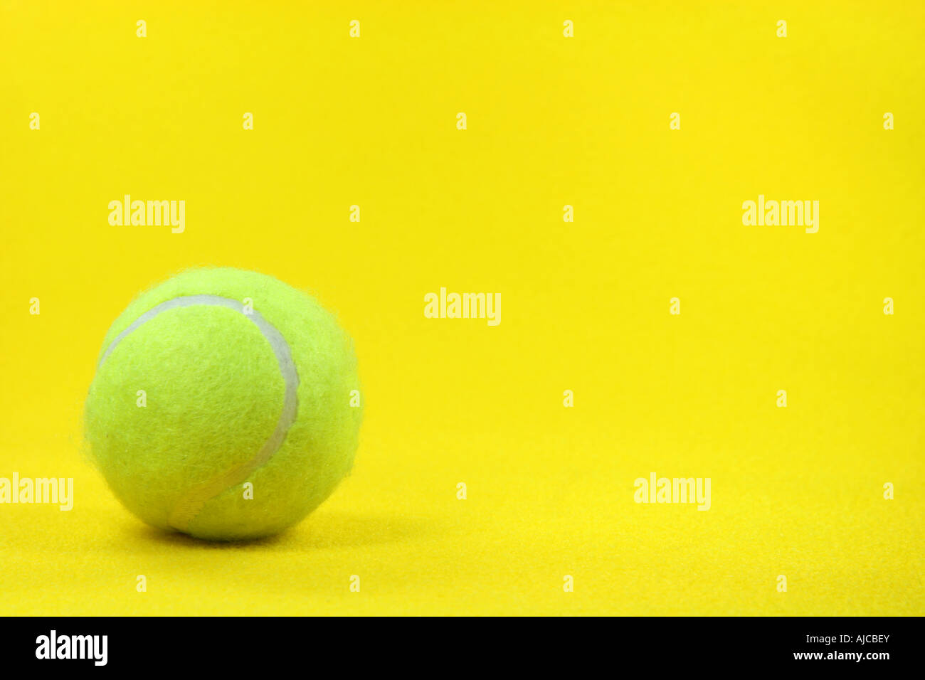 One Yellow Tennis Ball In The Left Side With Yellow Background