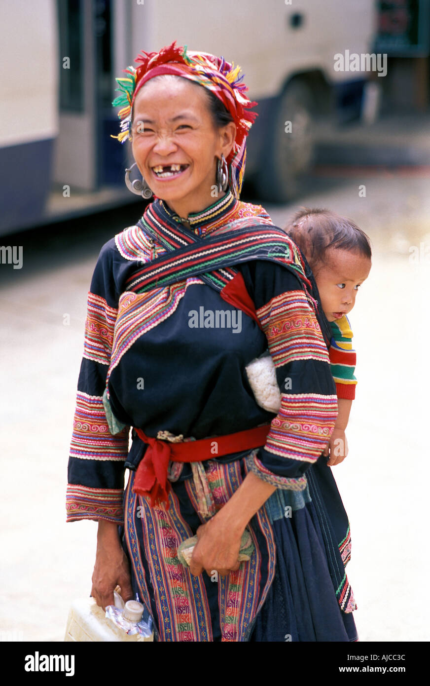Woman with child from the Flower Hmnog hilltribe in distinctive tribal costume Sapa Vietnam - Stock Image