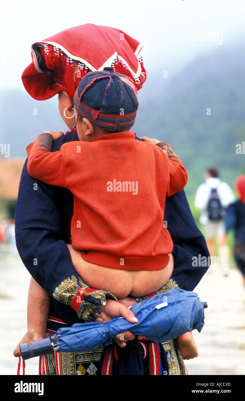 Woman with child from the Red Dao Dzao hilltribe in distinctive tribal costume Sapa Vietnam - Stock Image