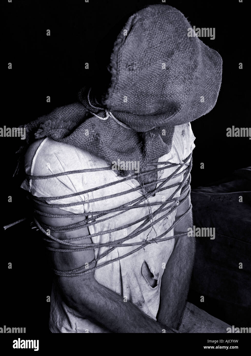 Man in his twenties bound with rope. - Stock Image