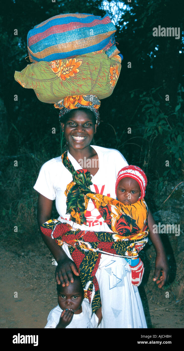 A young woman of Malawi carrying a large basket and bundle on her head and a baby bound in a cloth over her shoulder - Stock Image