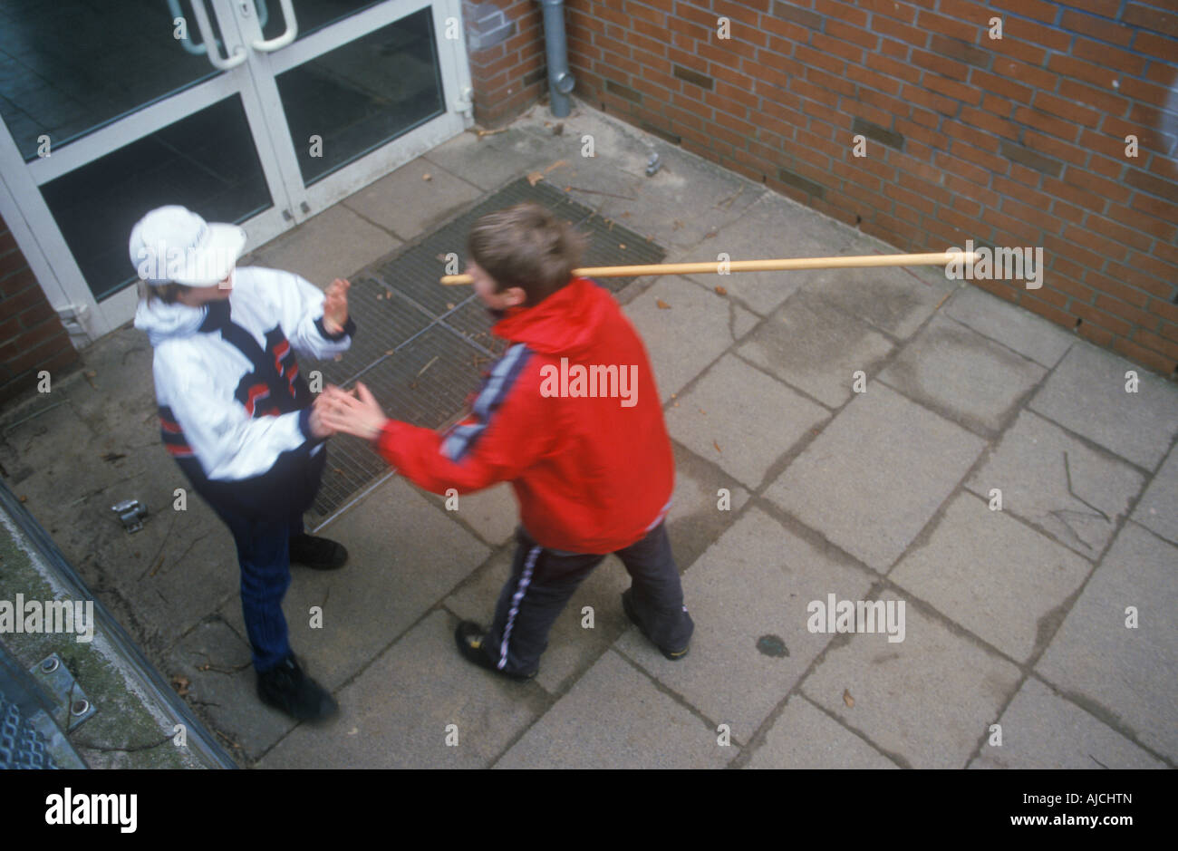a young boy attacking another one with a stick at a schoolyard - Stock Image