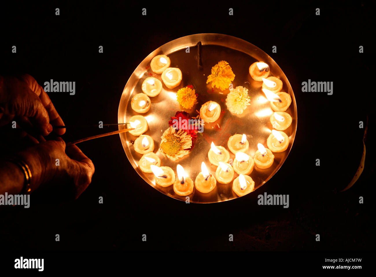 A devotee lighting earthen lamps for a religious ceremony - Stock Image