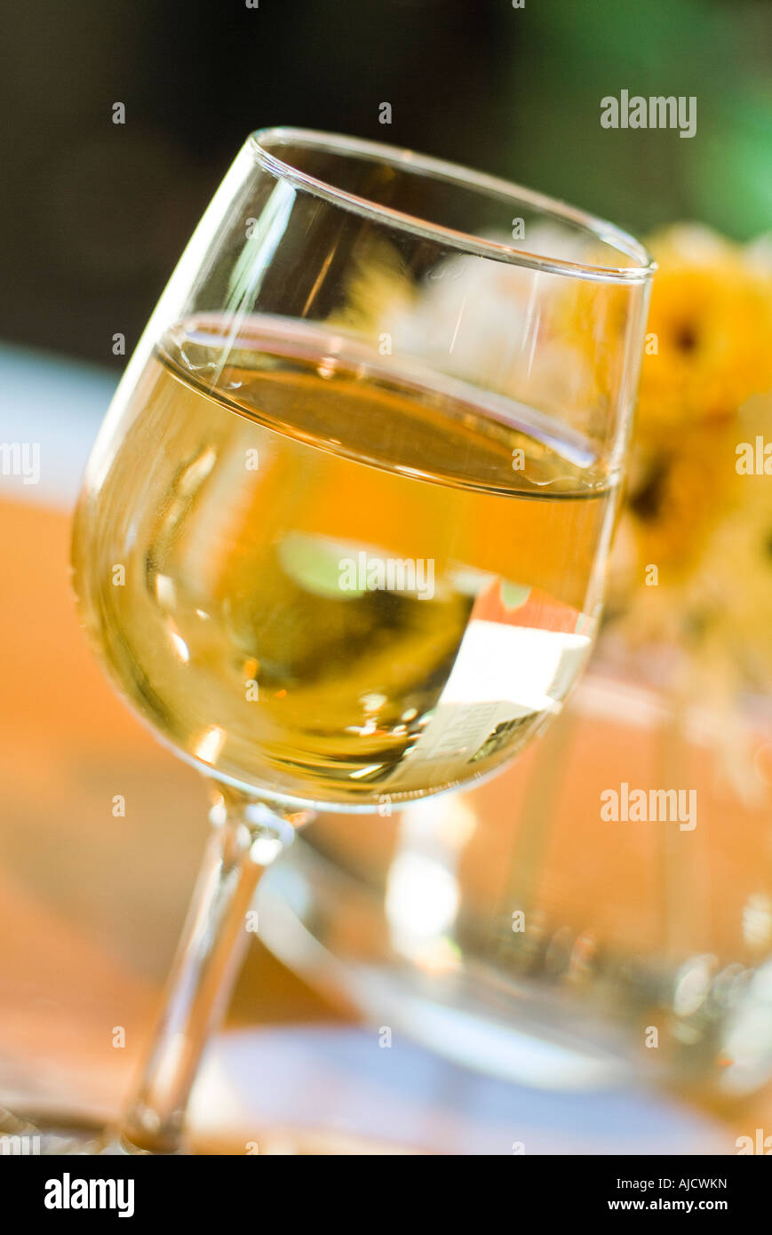 Glass of white wine with spring flowers sitting on table stock photo glass of white wine with spring flowers sitting on table mightylinksfo