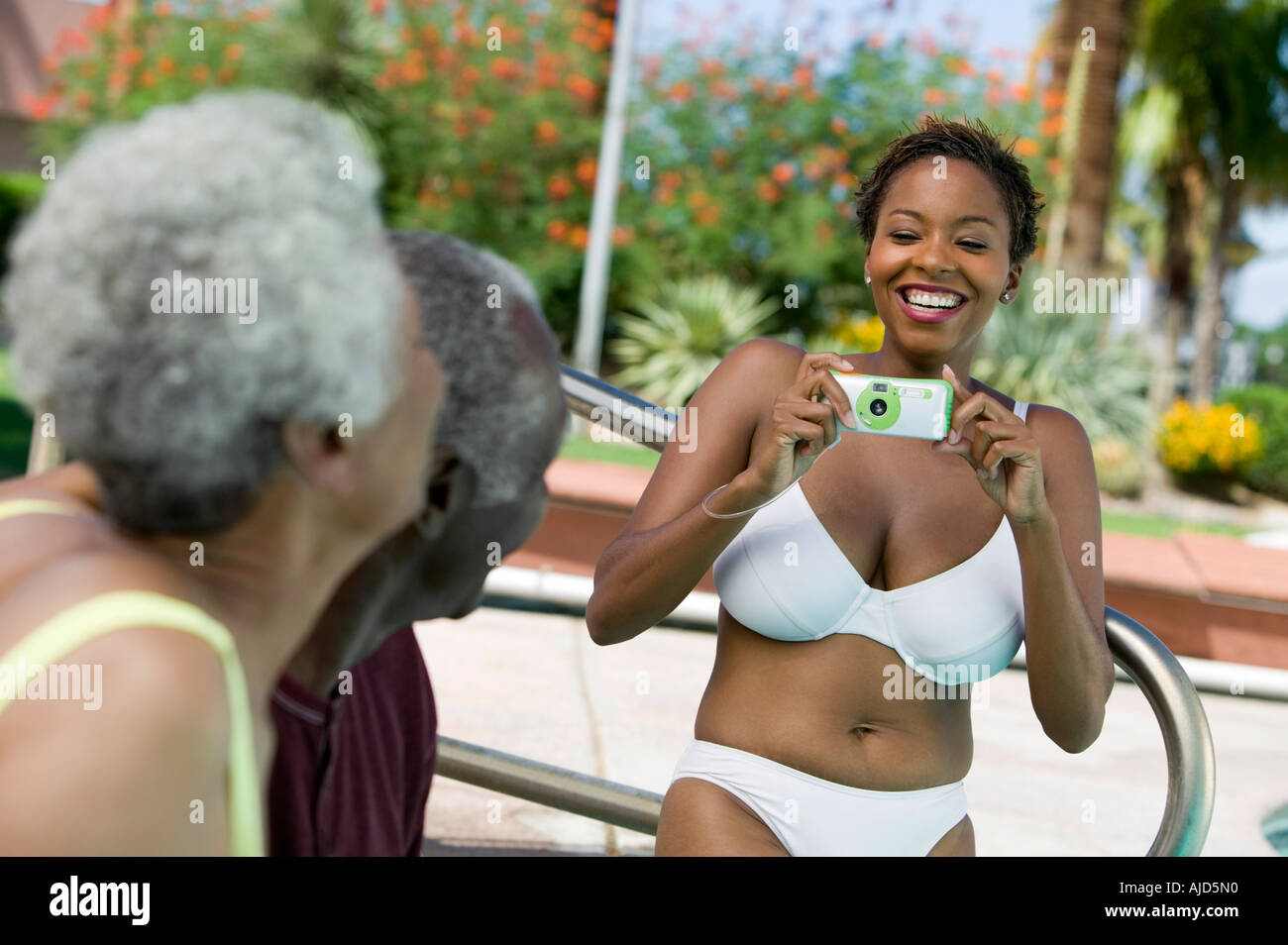 5a6b2dfdf913d Woman wearing bikini photographing senior couple outdoors. - Stock Image