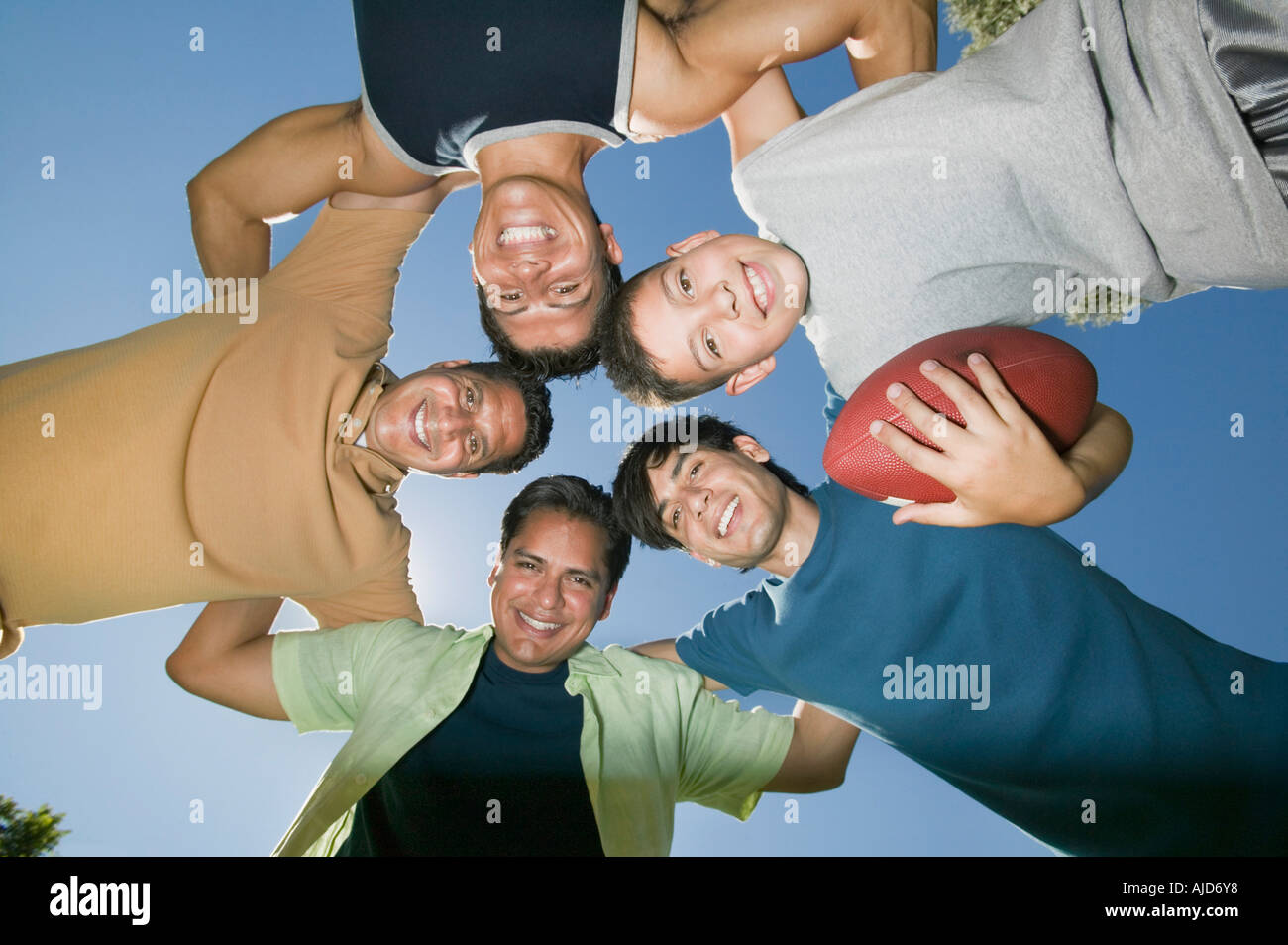 Boy (13-15) holding football, with brothers and father in huddle, view from below. - Stock Image