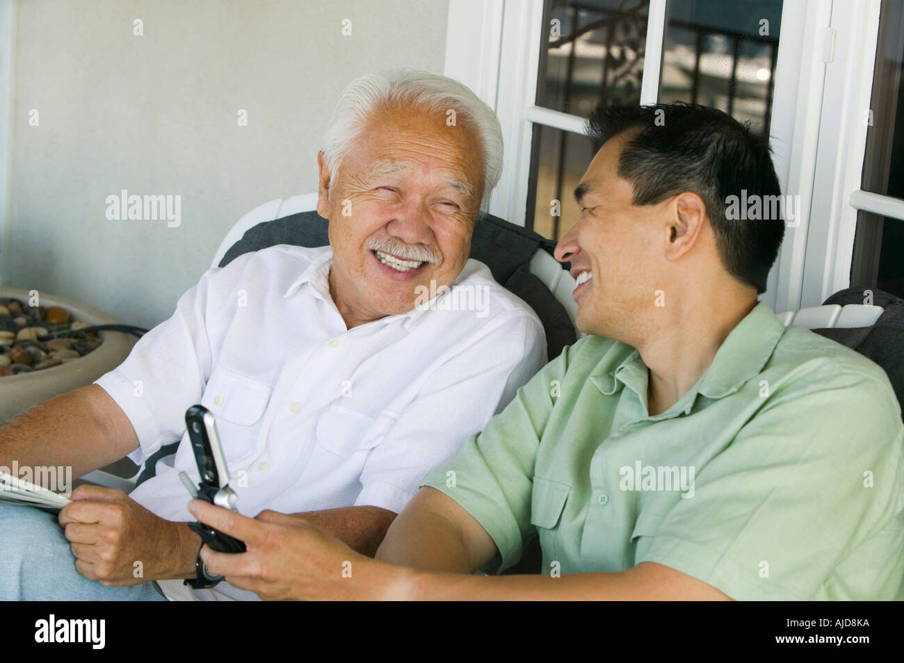 Father and son laughing outside home - Stock Image