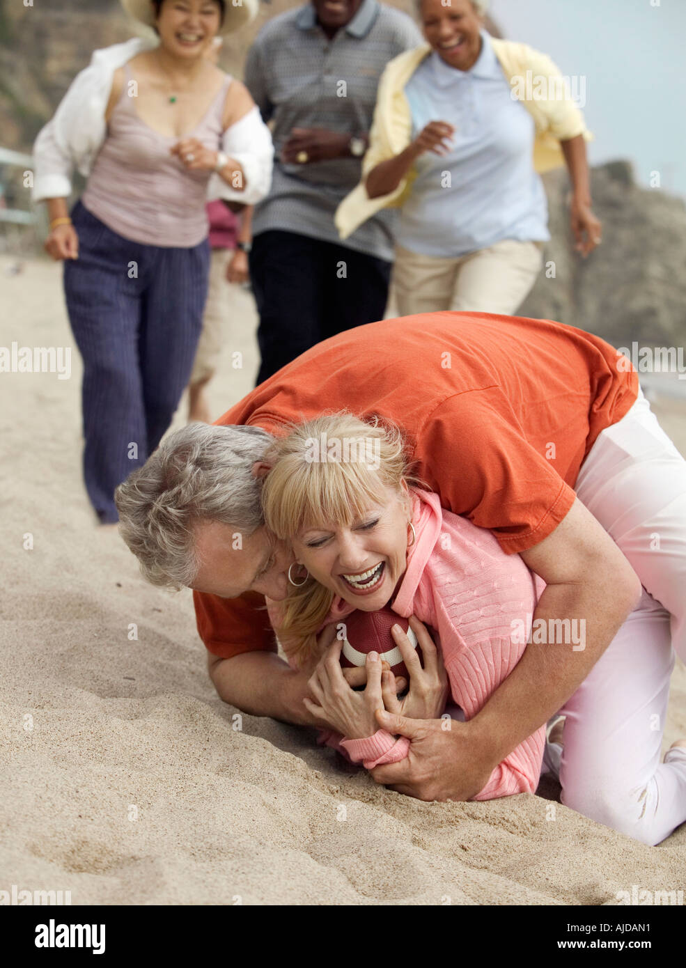 Man tackling woman with football on beach - Stock Image