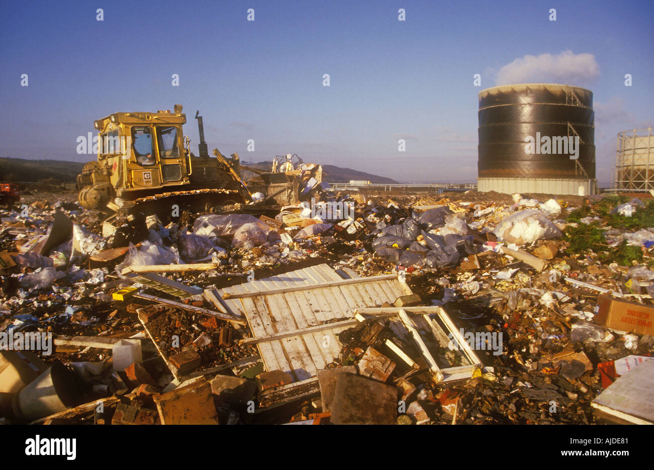 Bulldozer on landfill site with gasworks in background Wales UK - Stock Image