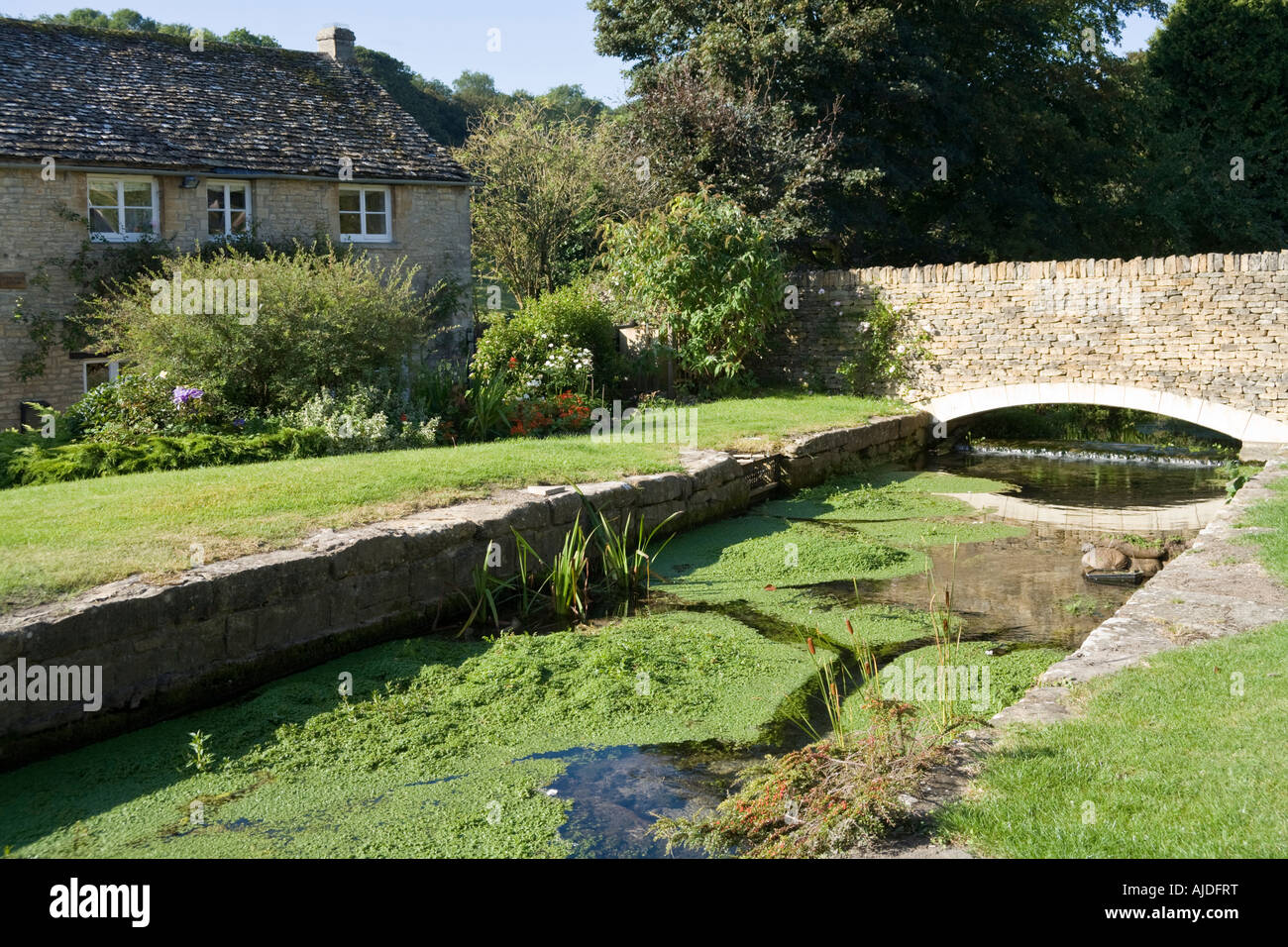 Glebe Field Cottage beside an old mill leat in the Cotswold town of Northleach, Gloucestershire - Stock Image