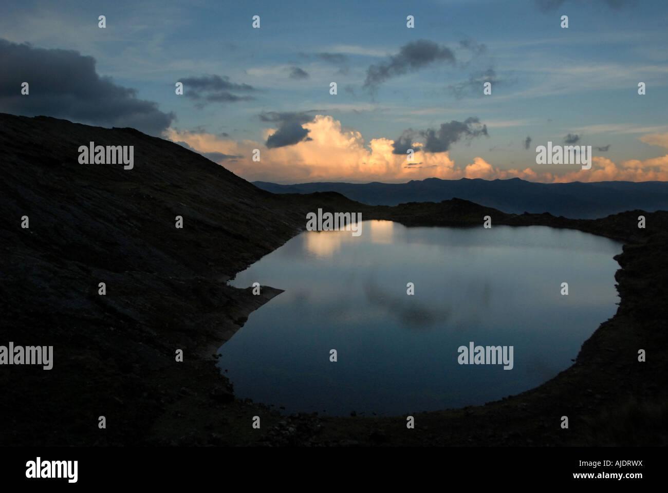 Sunrise is reflected off of Lake Chillata located below Mt Illampu near Sorata, Bolivia, South America. - Stock Image
