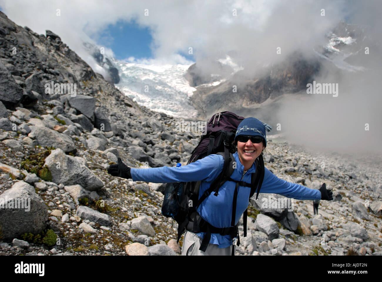 A woman smiles in front of Lagunas Glaciar at 5,038 meters below Mount Illampu near Sorata, Bolivia, South America. - Stock Image