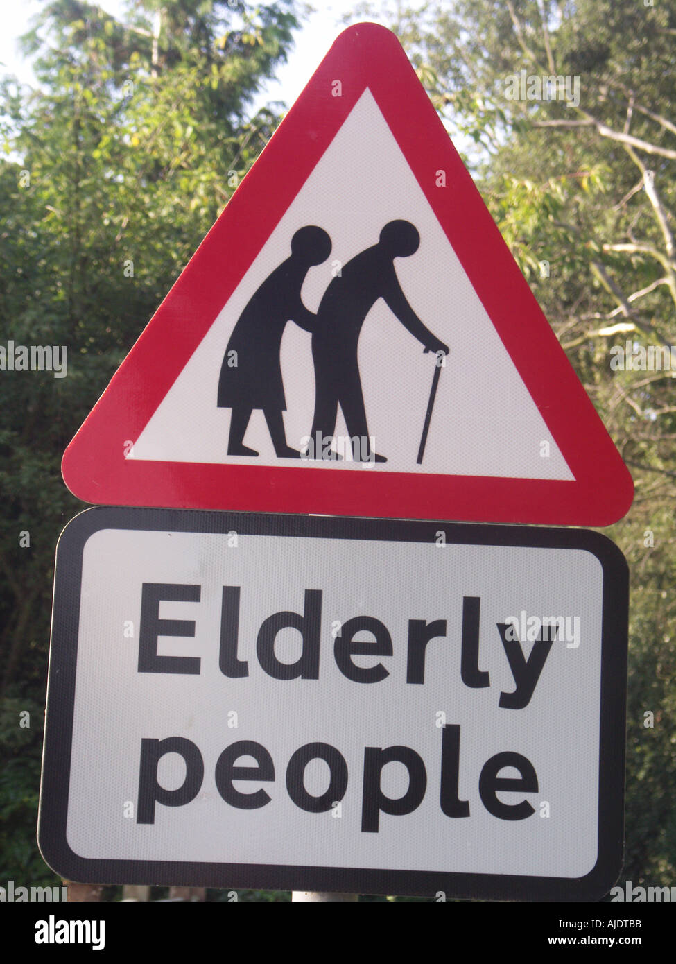 Elderly people crossing red triangular road sign - Stock Image