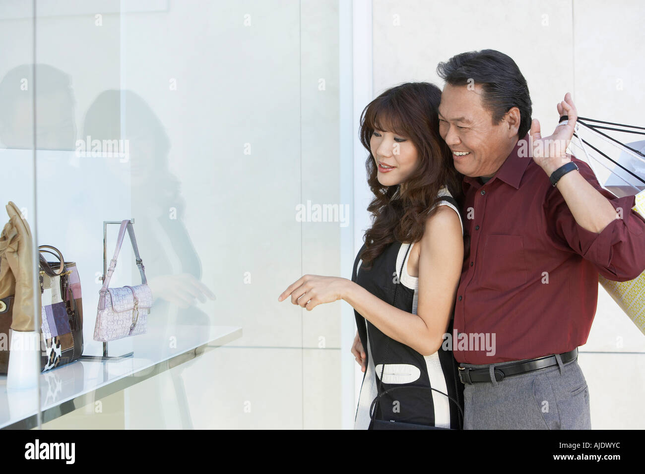 Couple looking at merchandise in shop window, arm around, holding shopping bags - Stock Image
