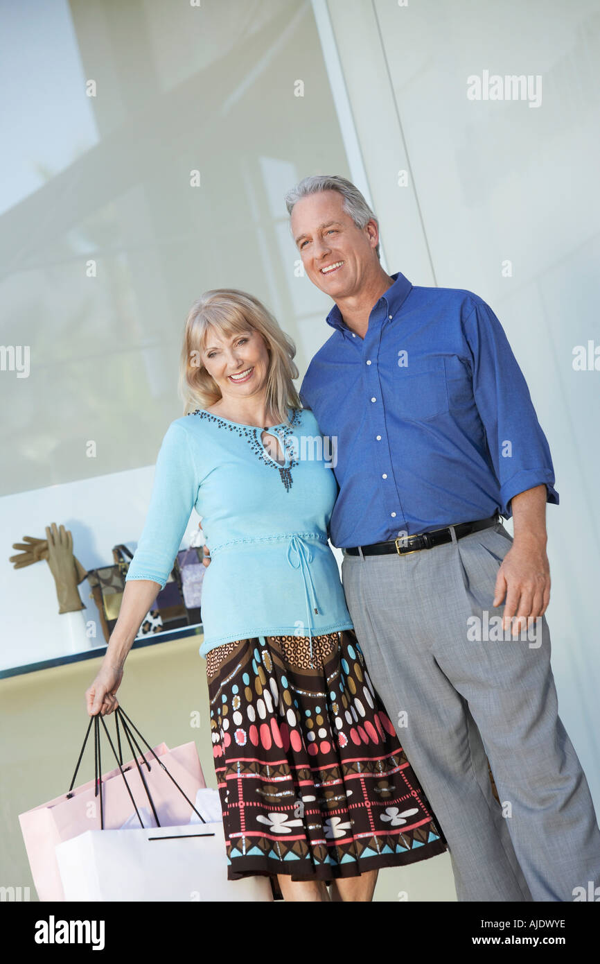 Couple standing outside shop, arm around each other, holding shopping bag - Stock Image