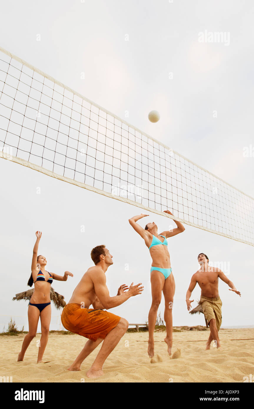 Woman Jumping for Volleyball During Game on Beach - Stock Image