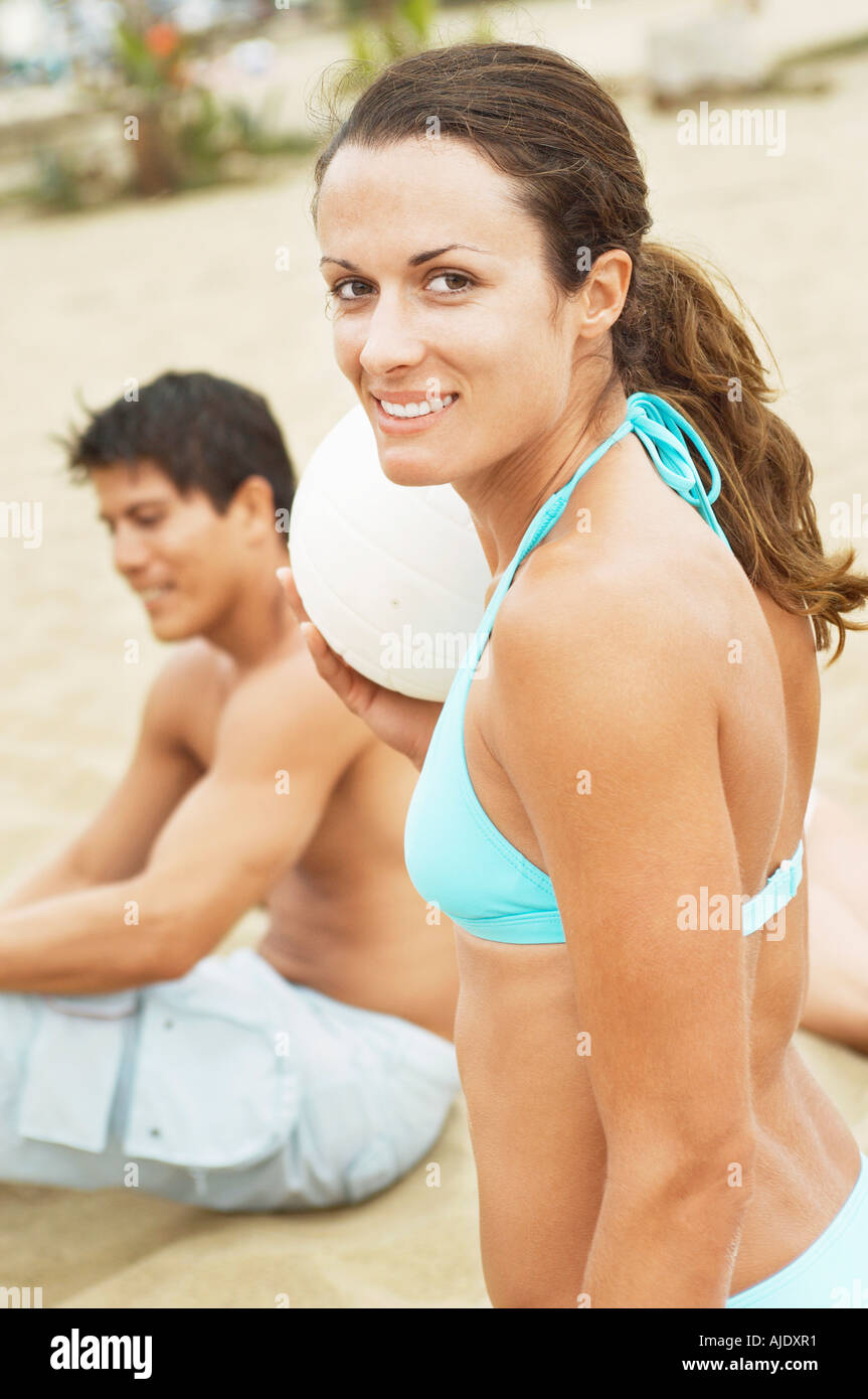 Woman in Bikini smiling, holding volleyball on Beach, portrait - Stock Image