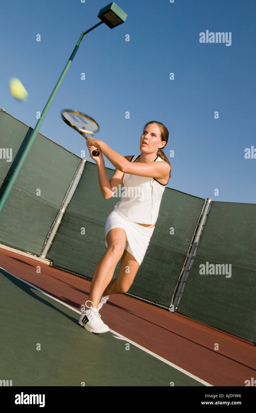 Tennis Player Hitting Backhand on tennis court - Stock Image