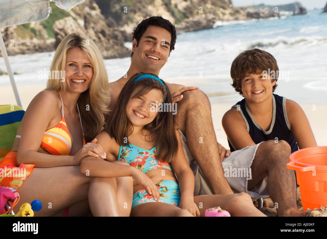 Family in swimwear sitting on beach, portrait - Stock Image