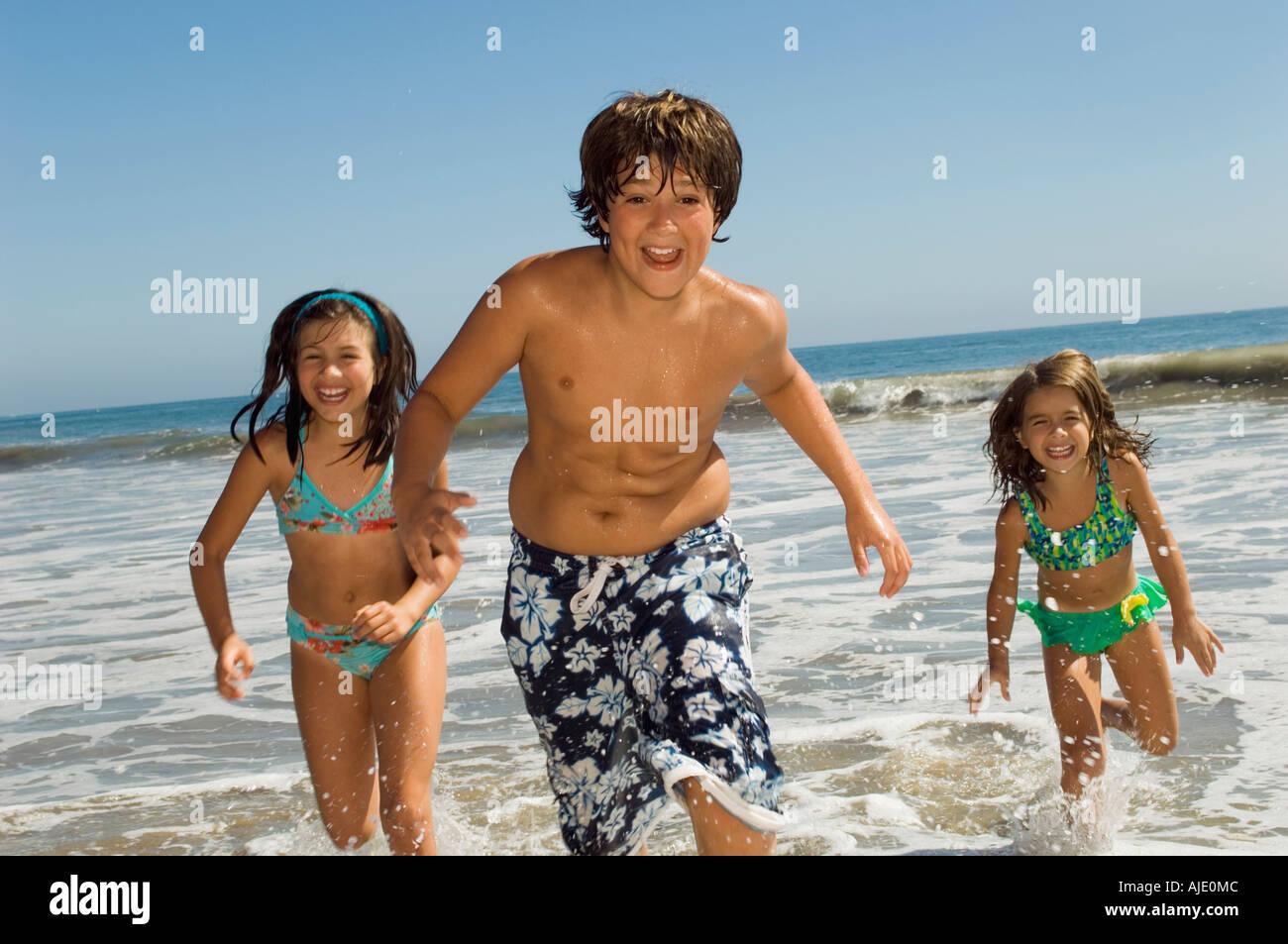 Children in swimwear running through waves - Stock Image