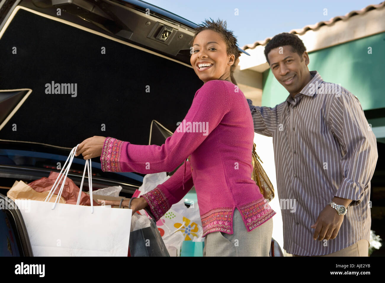 Couple putting shopping bags into boot of car, portrait - Stock Image