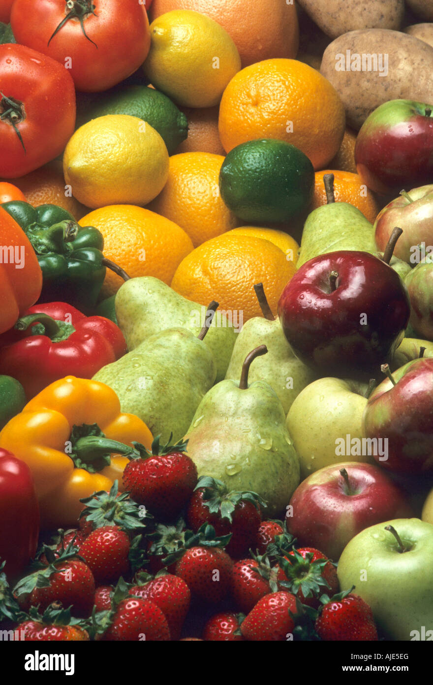 Cornucopia of mixed fruits and vegetables including apples pears strawberries oranges lemons limes peppers and potatoes - Stock Image
